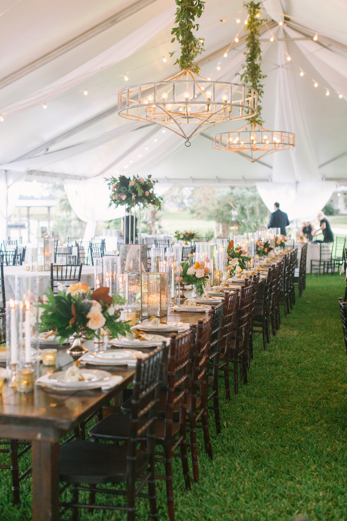 Southern Wedding Tent with Farm Tables Mahogany Chivari Chairs White Wash Chandelier Cafe Lighting Draping Candle Light