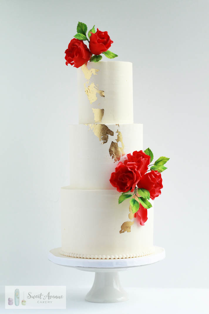 white wedding cake with gold leaf and red roses