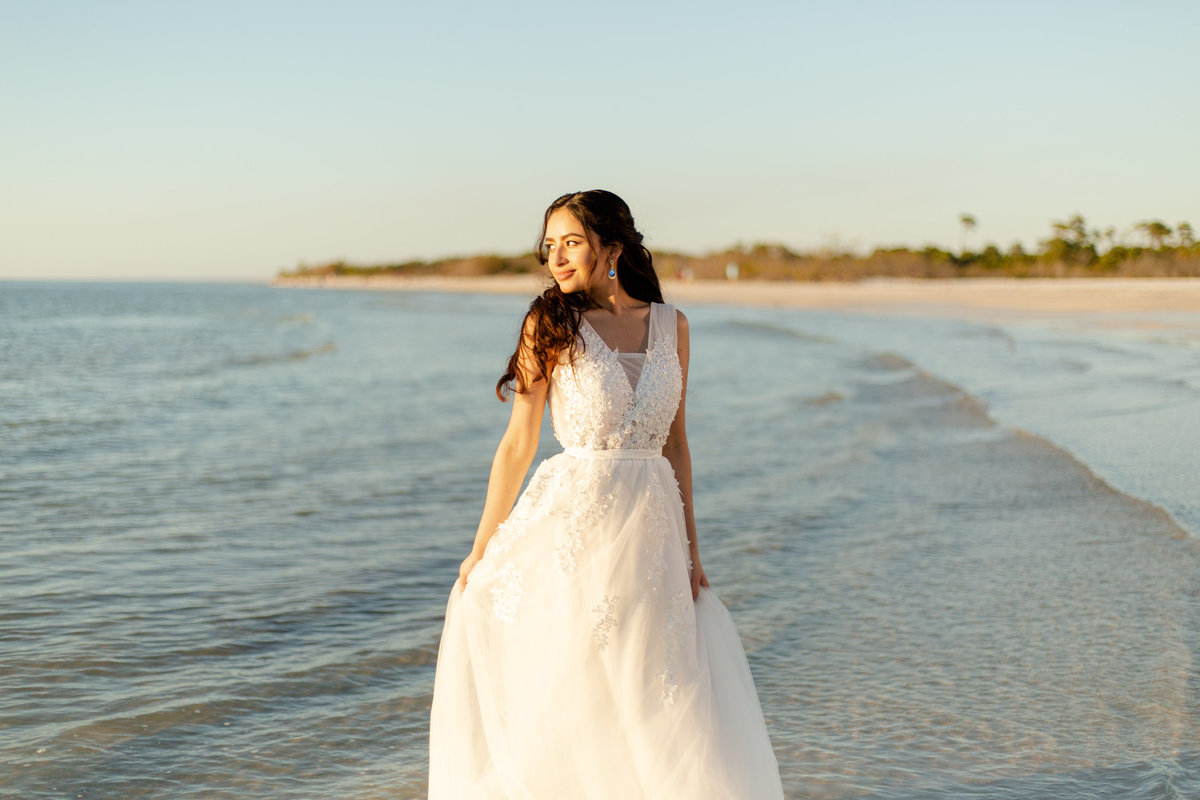 Glowing bride in white wedding dress stands in blue ocean on beach in Dunedin, Fl as she looks out at the sunset on her wedding day