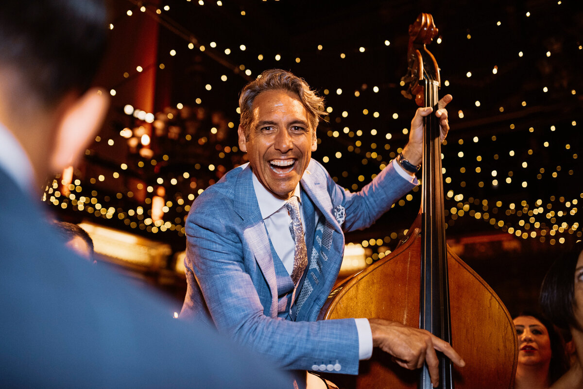 A smiling man plays the double bass under a canopy of fair lights at a wedding design by a london wedding planner.