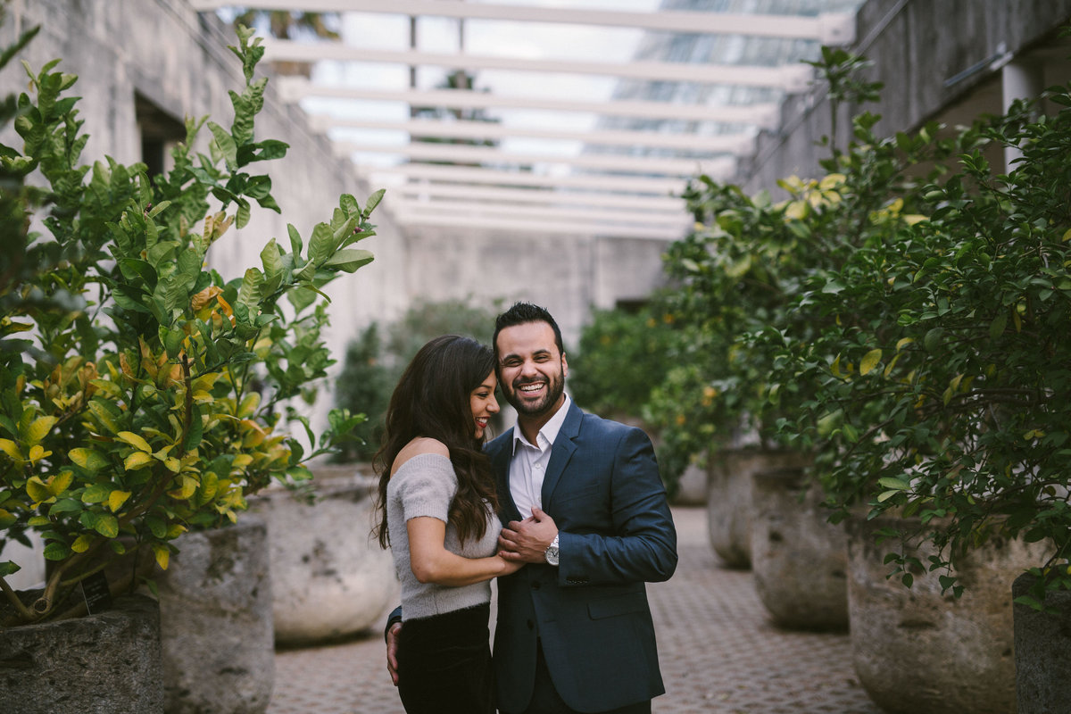 Engaged man and woman standing among citrus trees at the San Antonio Botanical Garden.