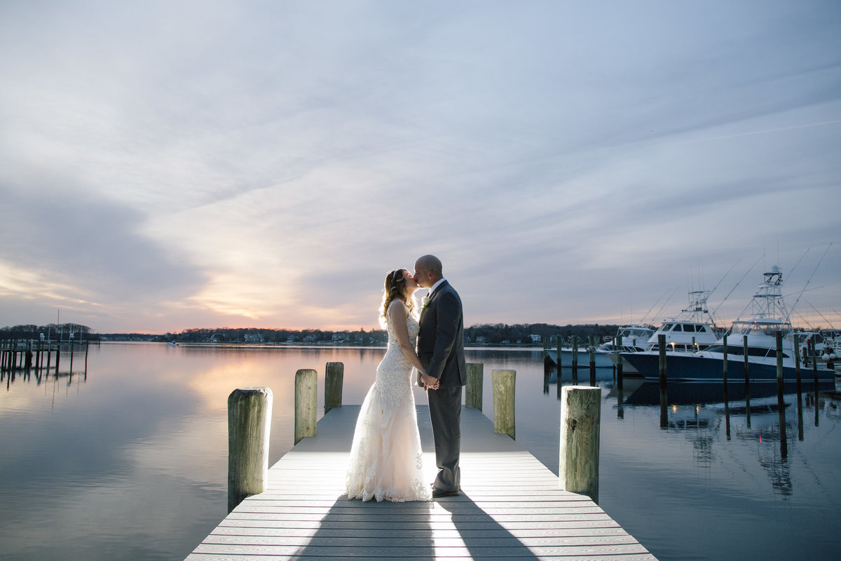 bride and groom kissing on dock at sunset at  clarks landing yacht club wedding