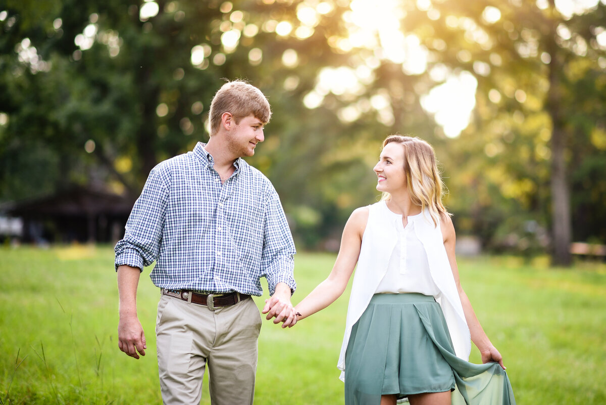 Beautiful Mississippi Engagement Photography: Couple walks hand-in-hand in a field during sunset