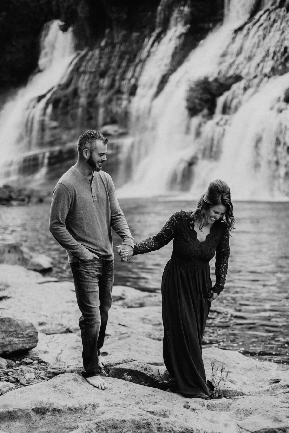 couple laughing and holding hands by a waterfall