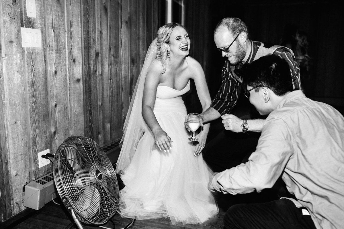 bride laughing while kneeling next to fan on the dance floor