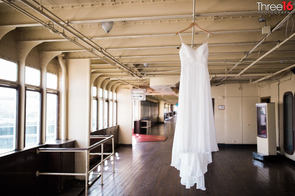 Brides wedding gown hanging from the Queen Mary