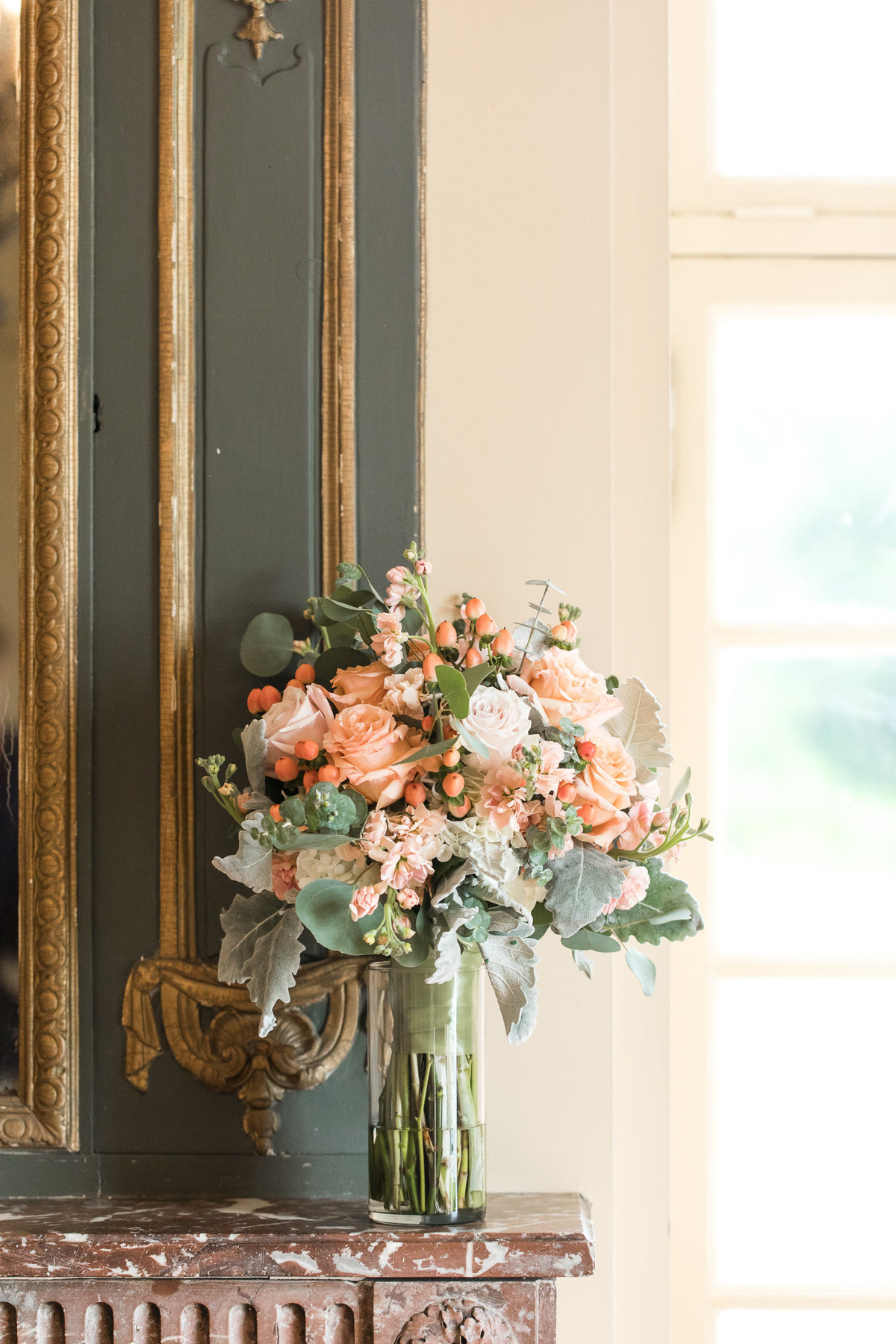 Peach rose bouquet sits on mantle at Glen Manor House