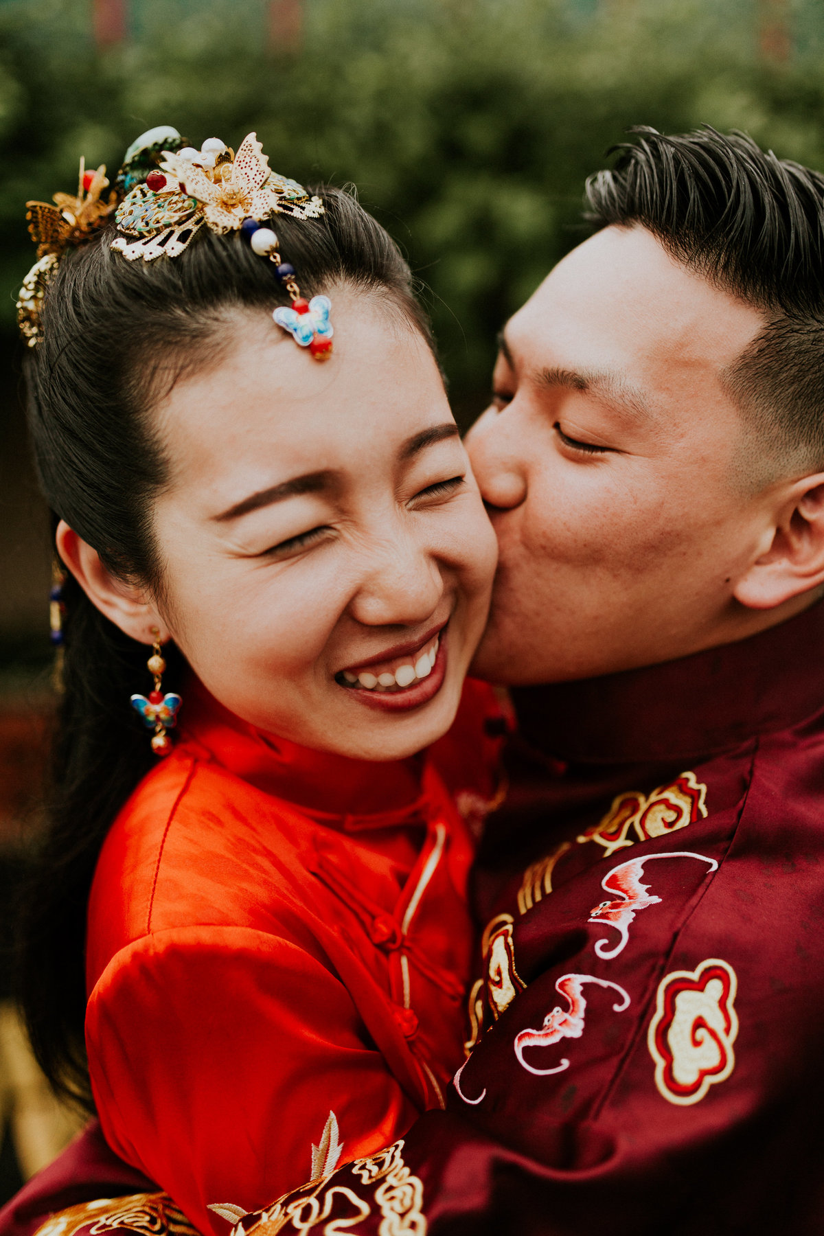 A groom kisses the bride on the cheek as she smiles in their bright red garments
