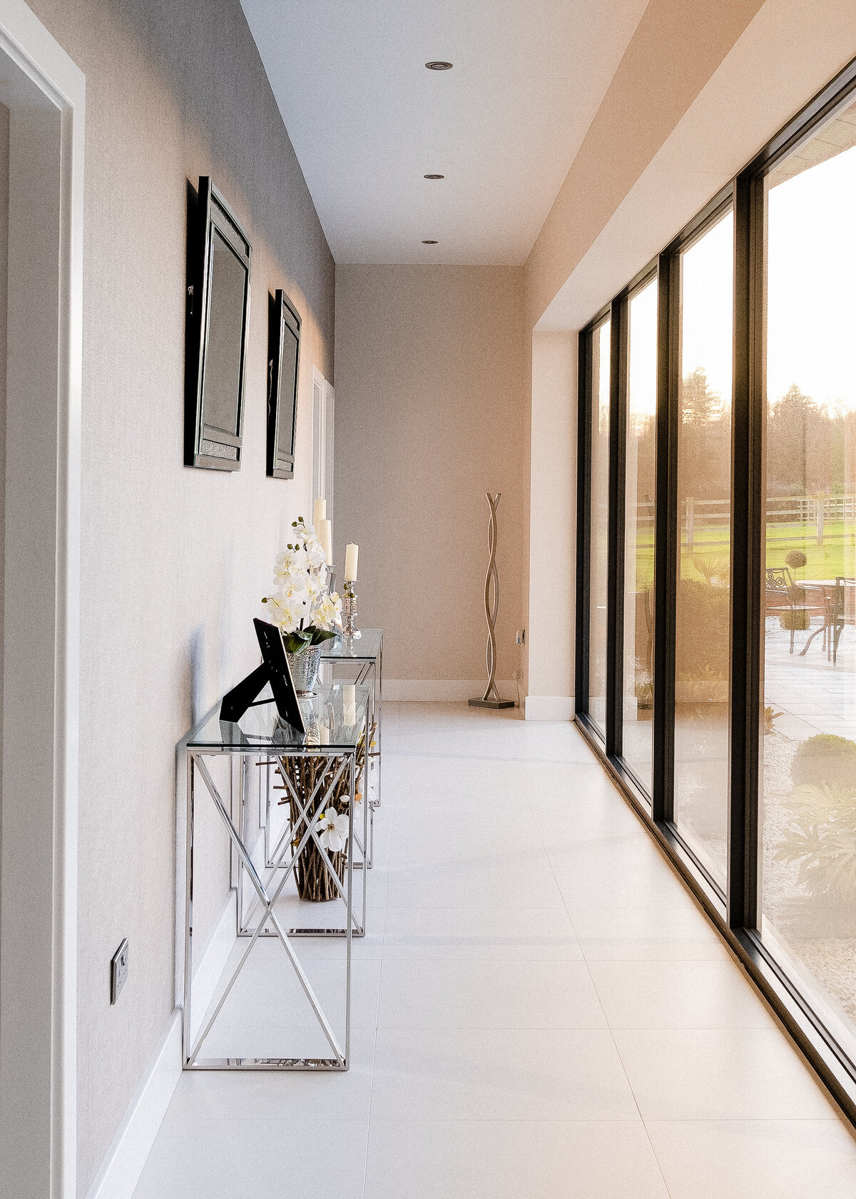 A minimalist hallway is accented with a silver console table and black patio doors.