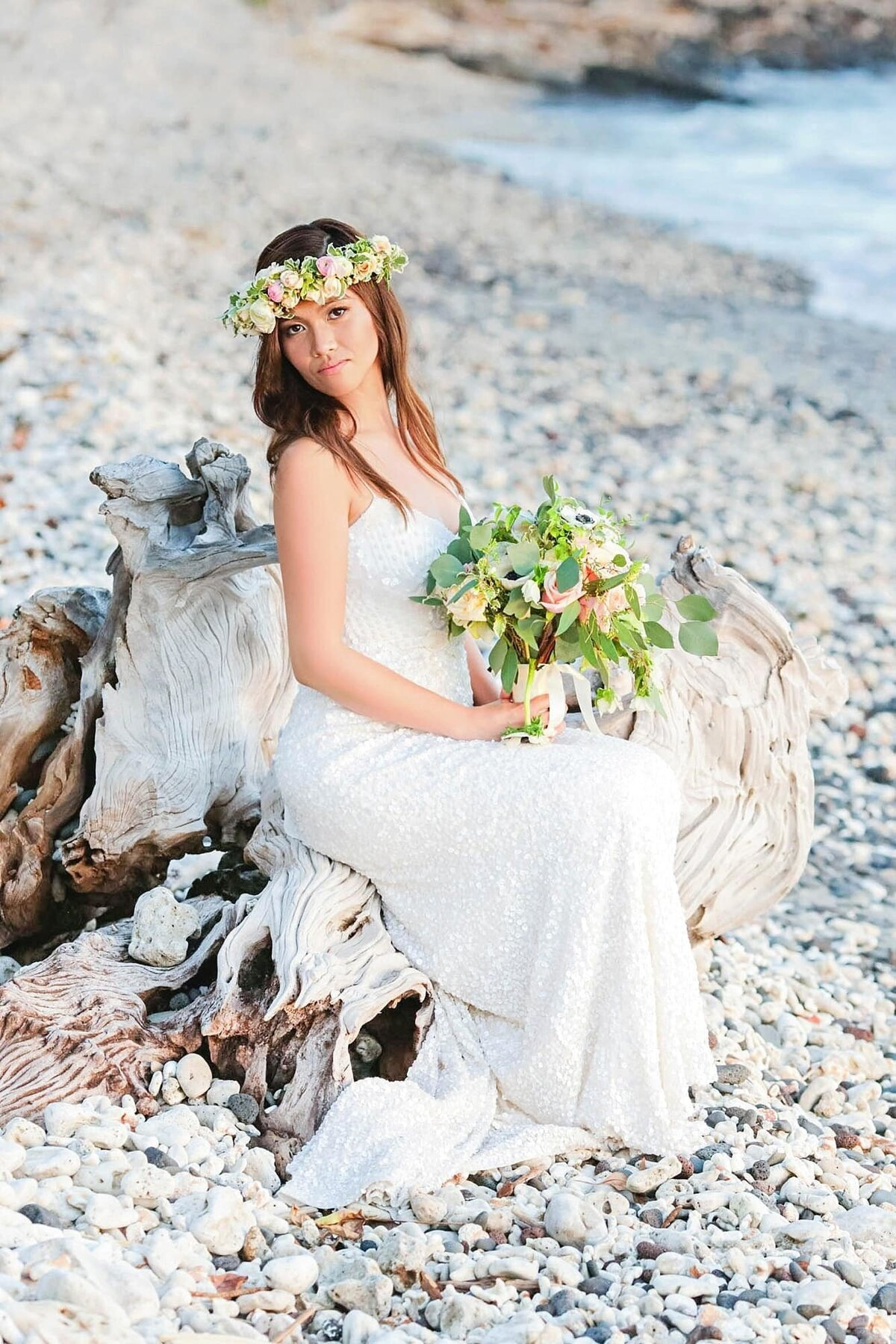 Bride sits on log at the beach fronting Olowalu Plantation House on Maui