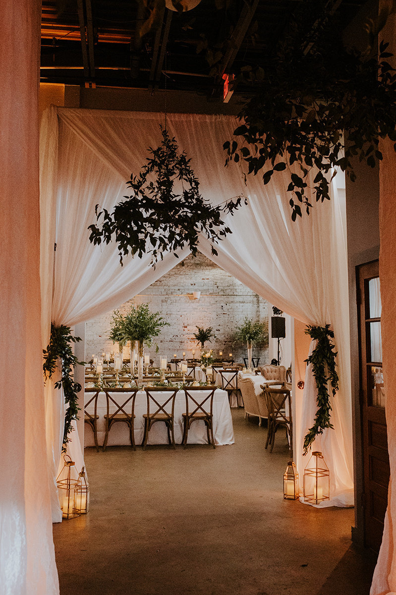 Greenery chandeliers with white draping into reception