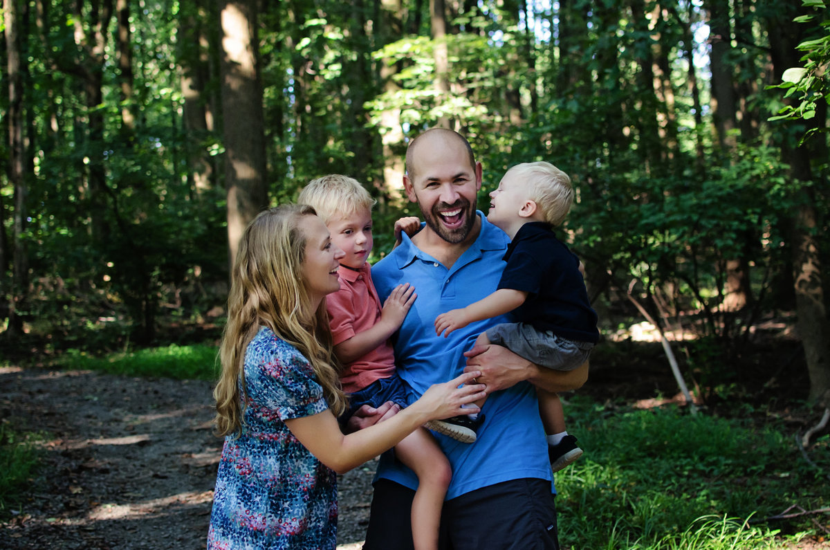 Portrait of a family of four laughing during a lifestyle session at Nottoway Park in Northern Virginia taken by Sarah Alice Photography