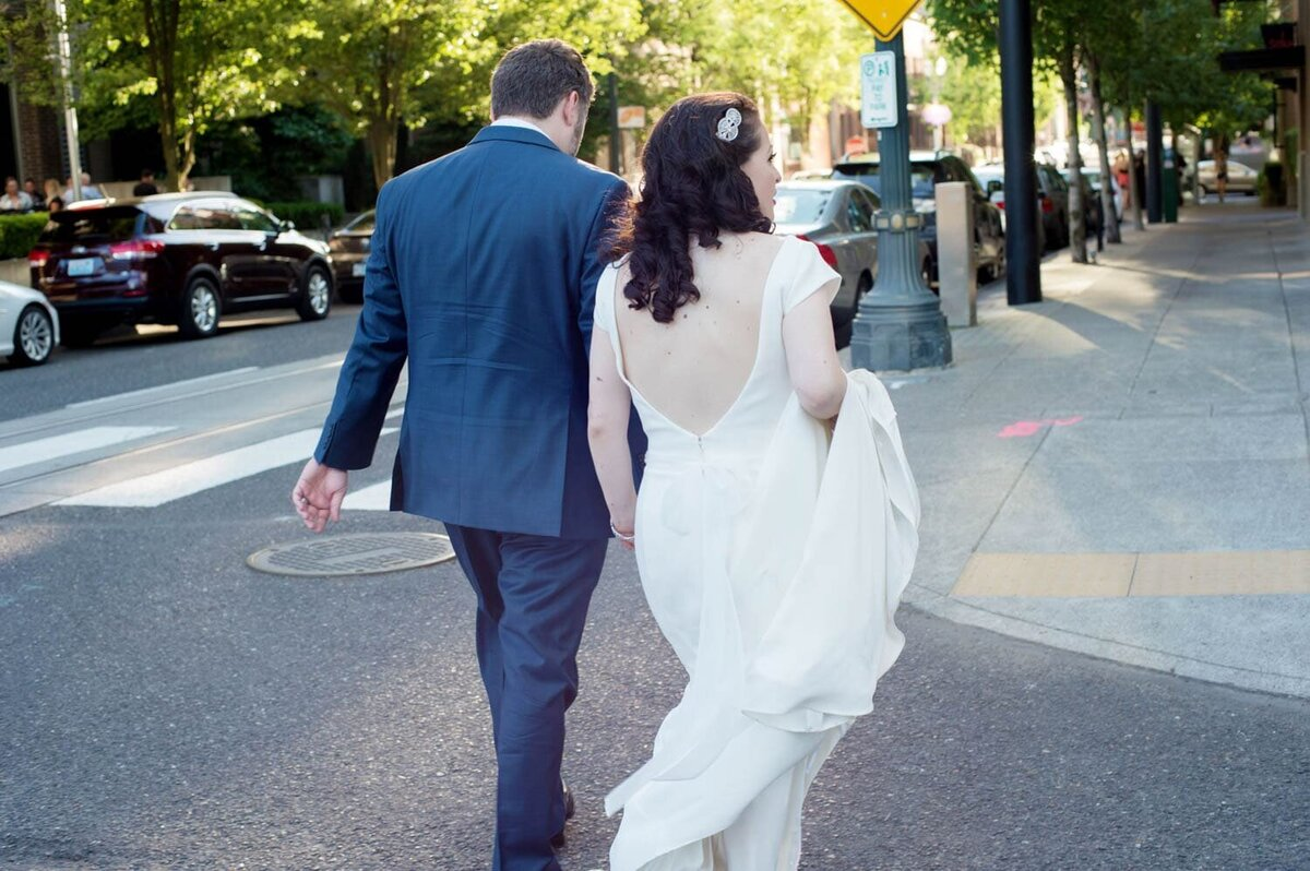 a bride and groom walk through downtown portland