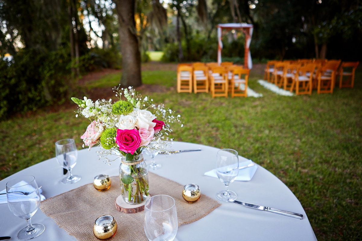 Outdoor wedding reception table with pink flower centerpiece, with ceremony chairs and arbor in the background, in Savannah, GA