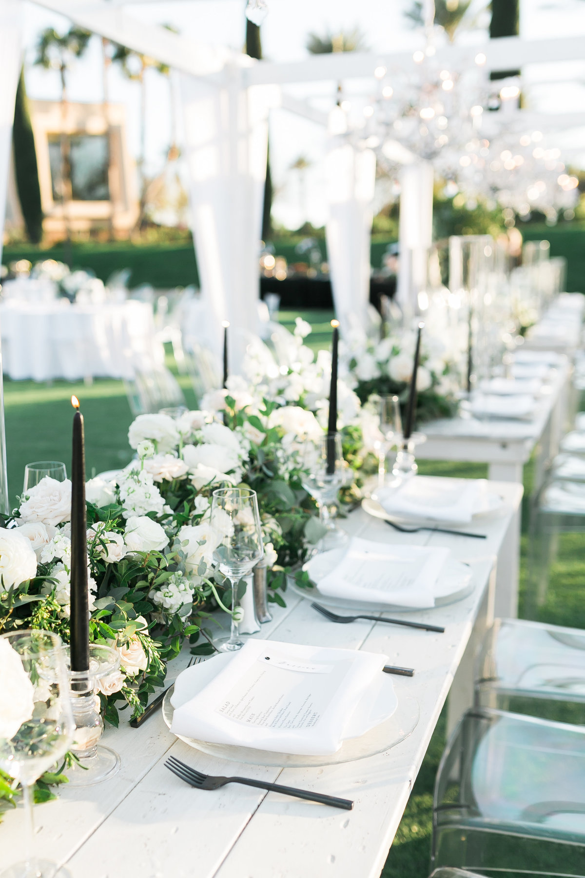 a wedding reception photo with white long tables, black tapered candles, black flatware and white and greenery floral centerpieces below canopies with hanging crystal chandeliers at a wedding at Green Valley Ranch Resort and Spa in Las Vegas