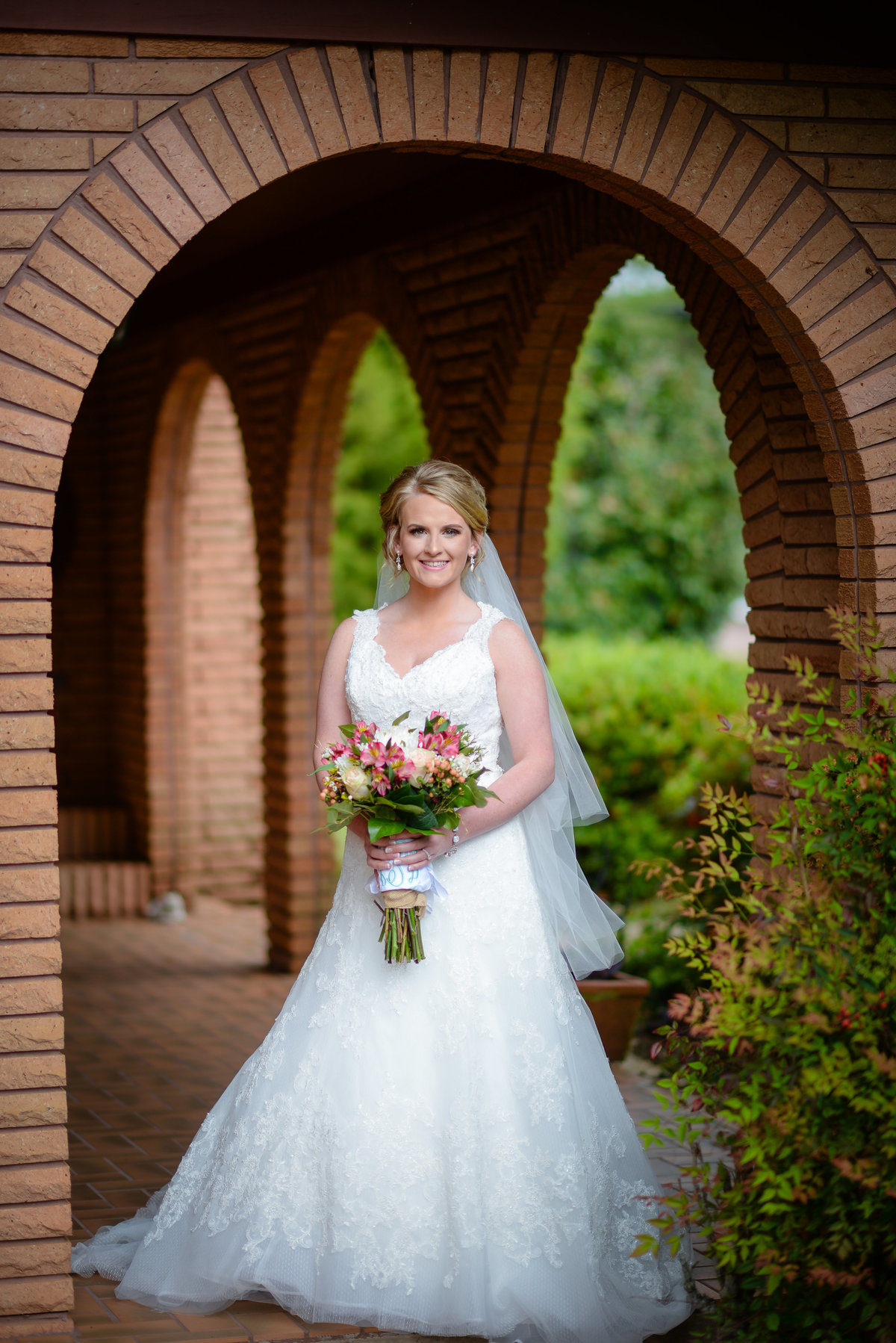Beautiful bridal portrait photography: Bride with bouquet under a Spanish arch before her Mississippi wedding