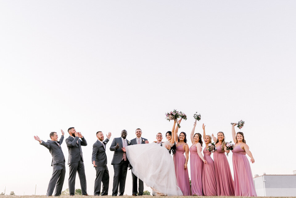 wedding party poses on a hill at sunset