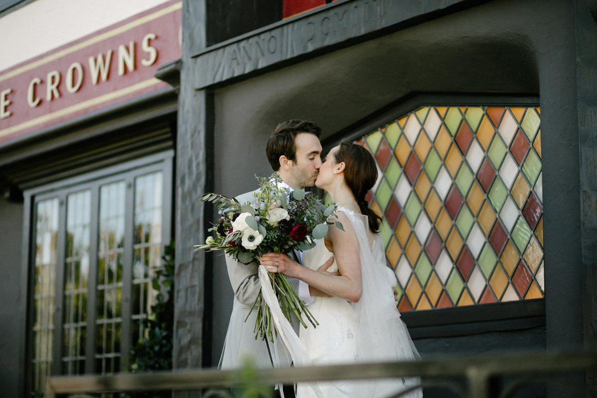 Bride and groom embracing in a kiss outside Five Crowns in California