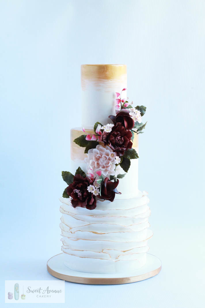 white fondant cake with gold details and burgundy sugar flower garland