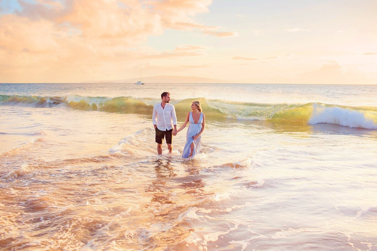 Expecting couple holds hands in the water during their portrait session on Maui