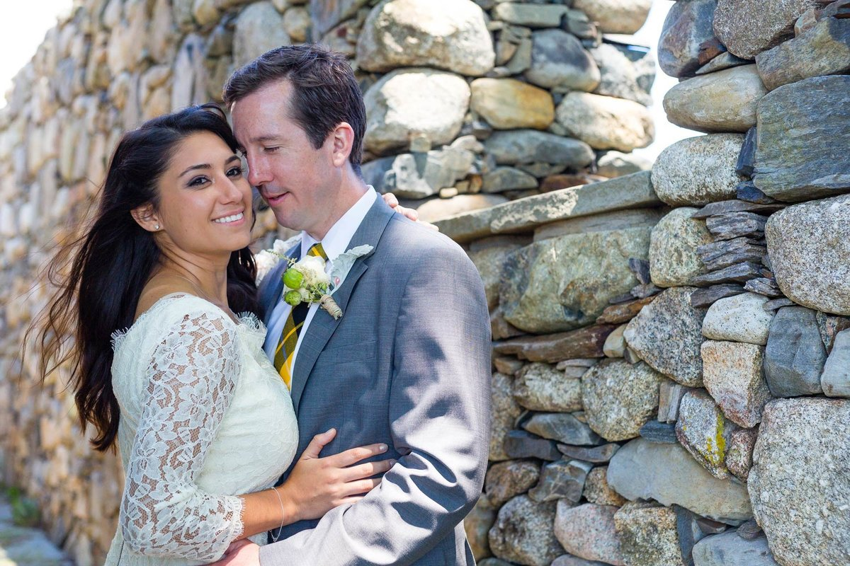 The bride and groom get in close by a stone wall in Kennebunkport Maine after eloping