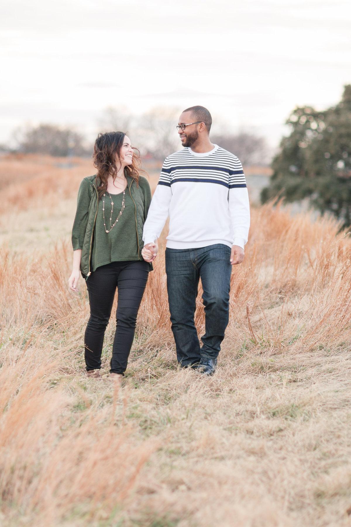 couple walking through tall grass at Fort Monroe Engagement Session