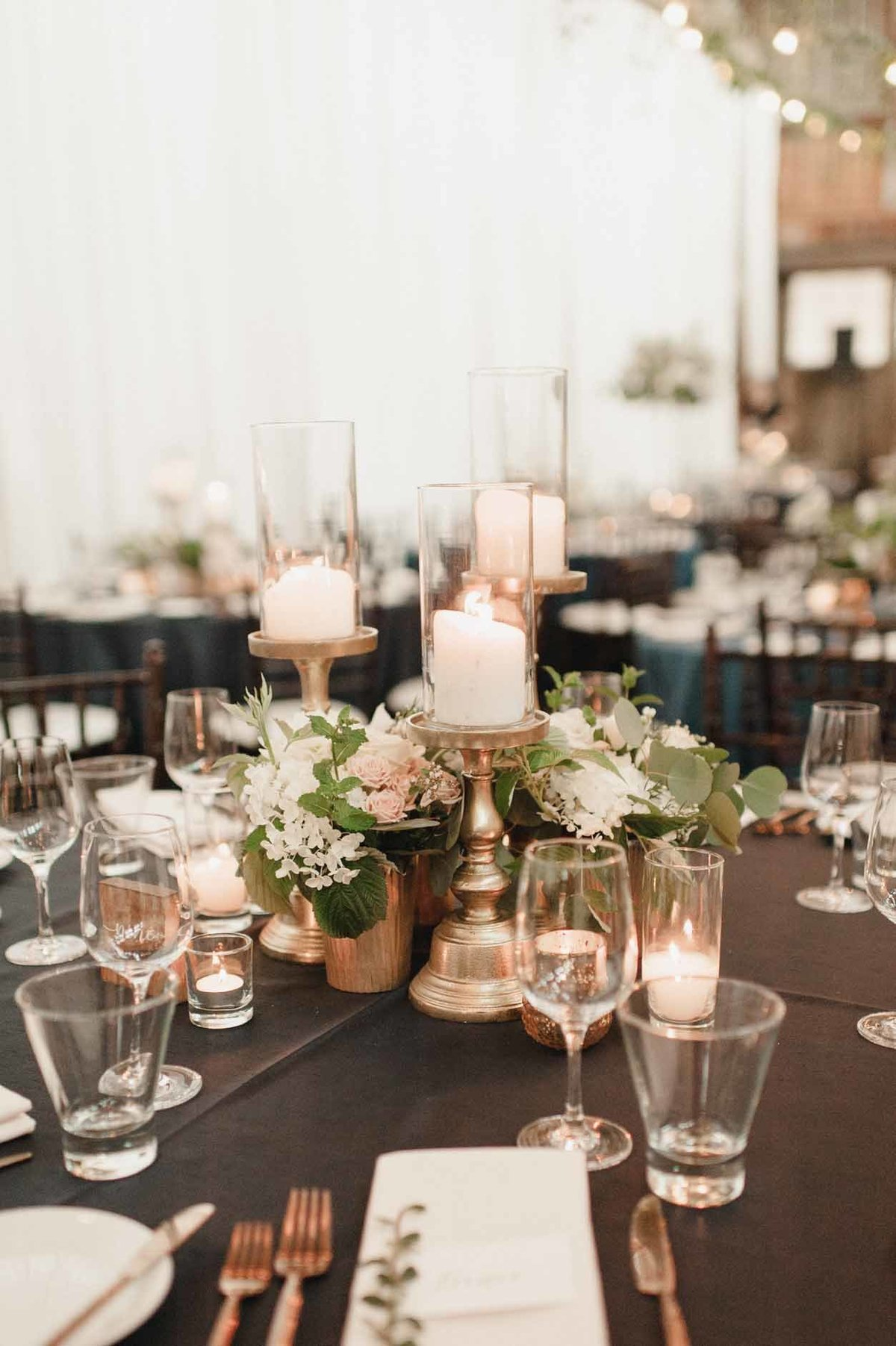 composite wedding centerpiece of gold hurricane candles and several small white and blush floral arrangements.