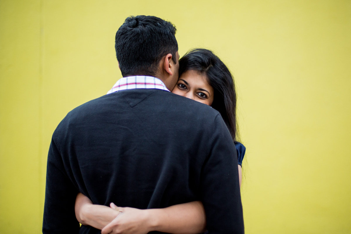 Indian fiancée looking over her fiancé's shoulder while on her engagement session with Expose The Heart Photography.