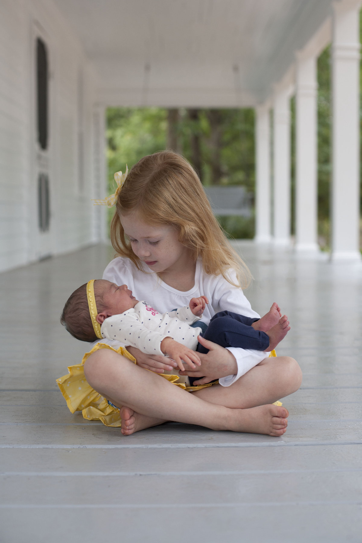 monroe_photographer_a_focused_life_photography_newborn_siblings_freemans_mill_park_gwinnett_county_toddler_girl_holding_newborn_baby_sister