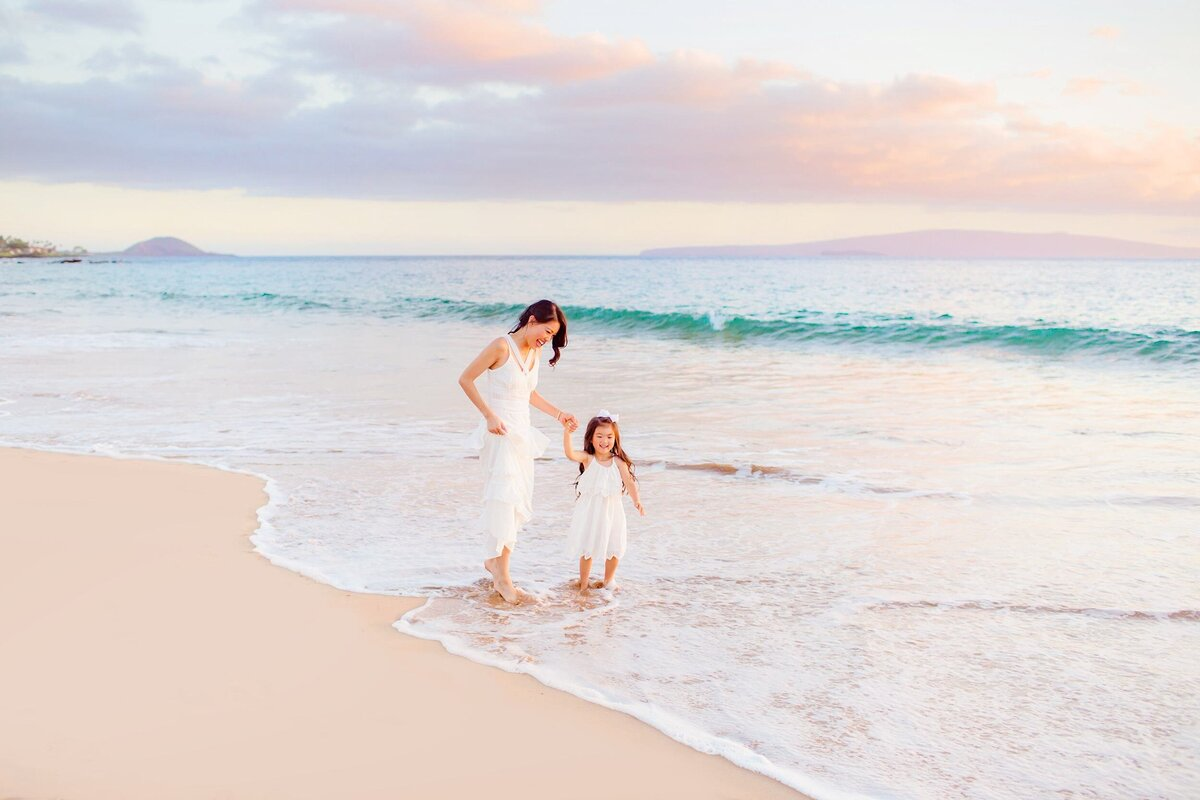 Mother and daughter hold hands on the beach at sunset during their Maui family photography session