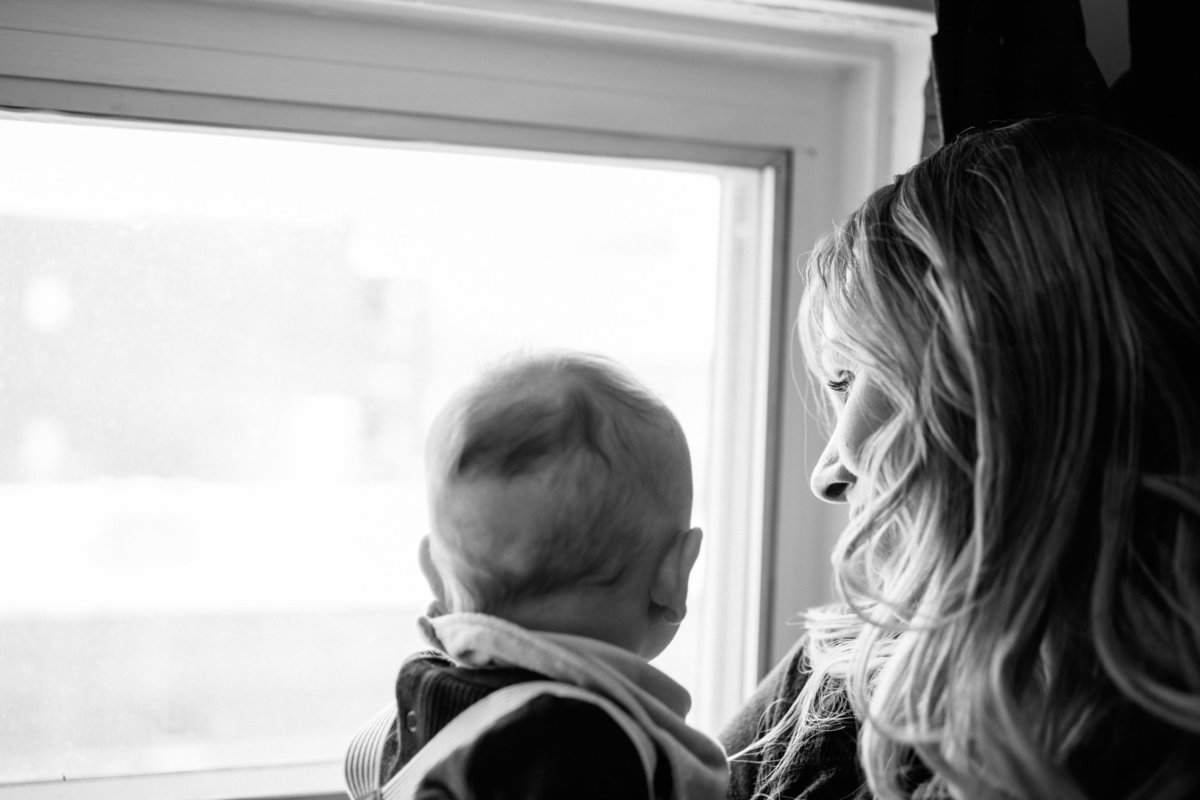 Mom looking out window with baby during lifestyle newborn session in Hamilton