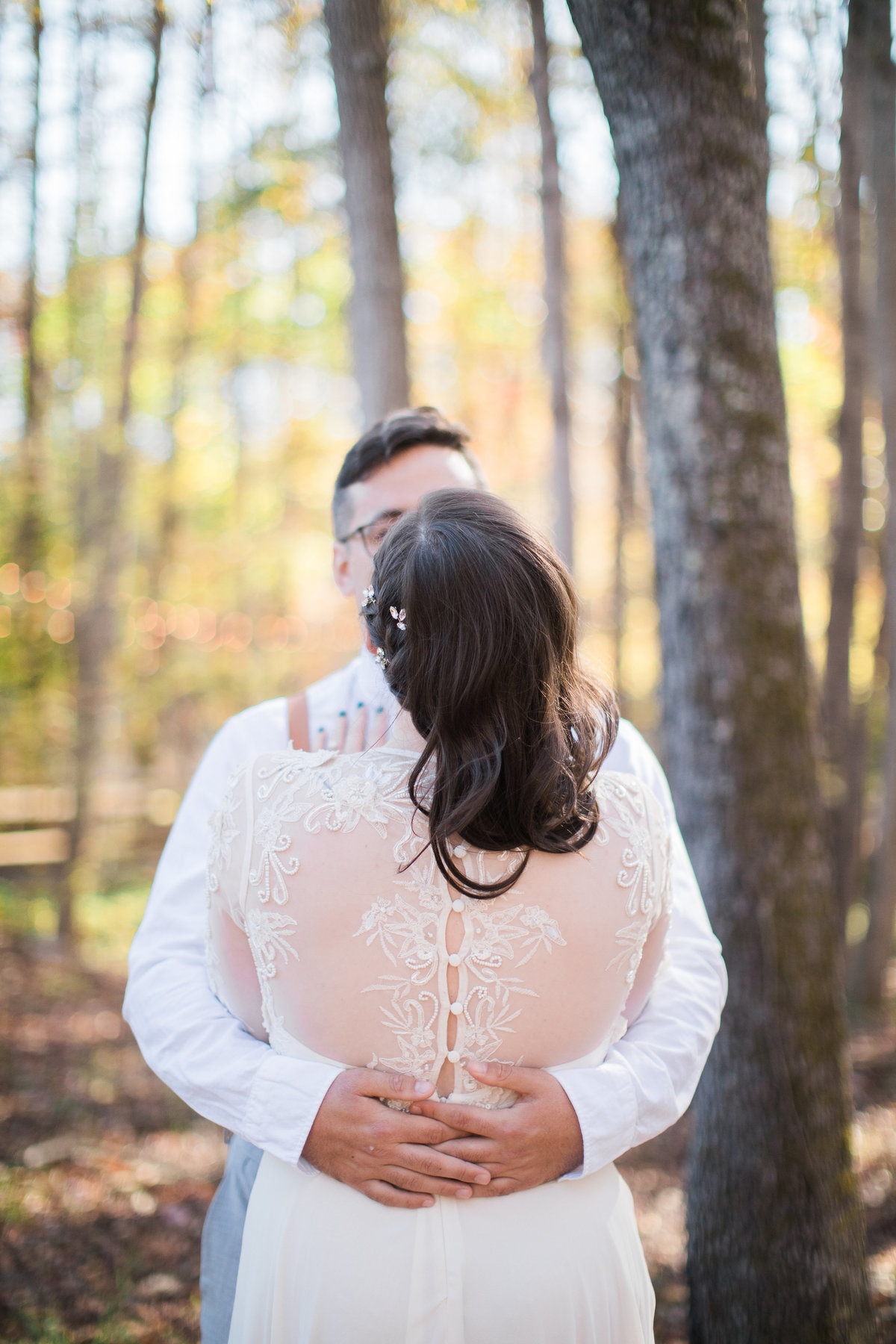 Wedding Photographer, bride and groom holding each other with her back toward the camera