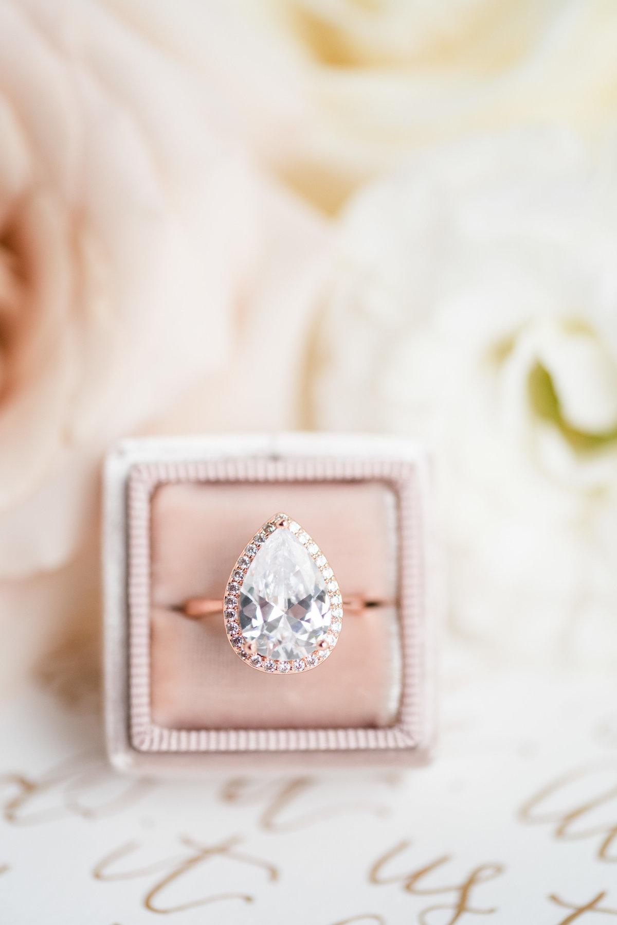 A teardrop diamond ring sits in a pink The Mrs. Box