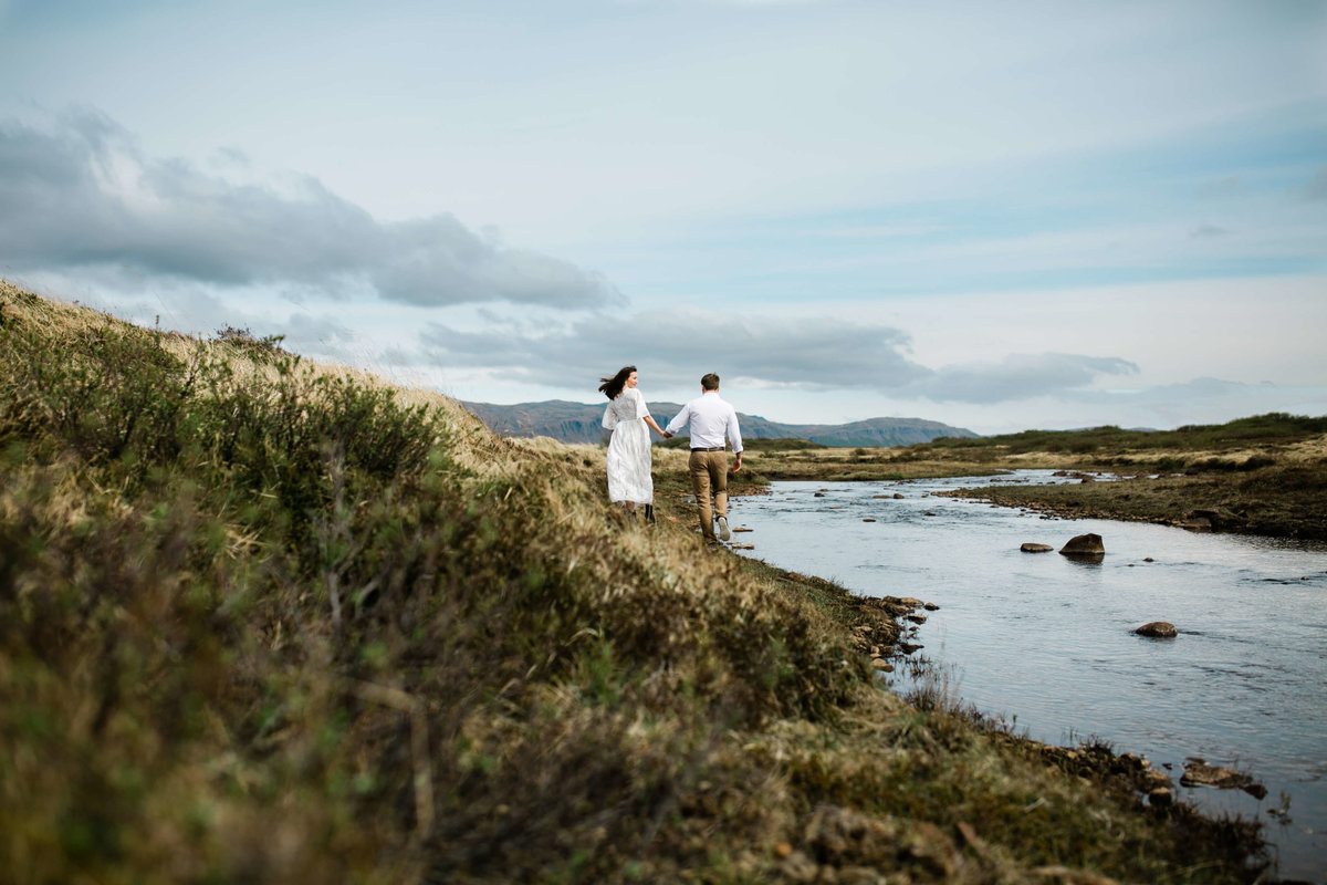 Hand in hand a couple walks along a n icelandic creek bed during their Iceland elopement.