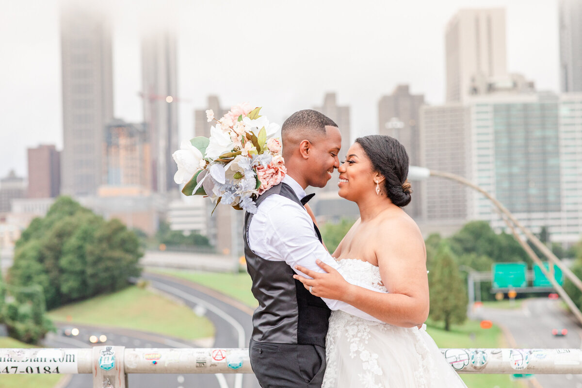 A black couple post on Jackson Street Bridge for their wedding in Atlanta Georgia with the skyline in the background.