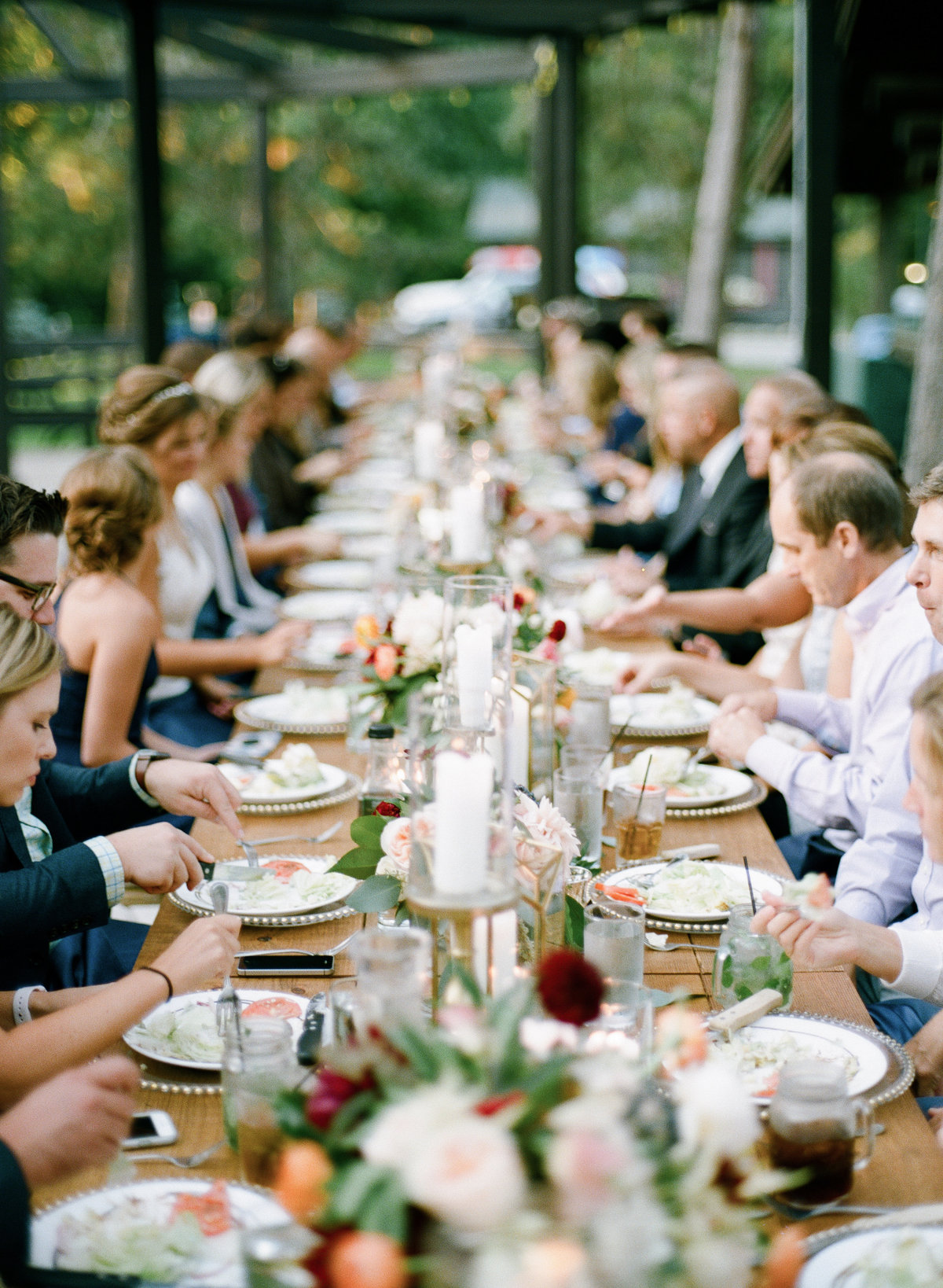 outdoor wedding reception all guests eat on long dining table beautifully designed