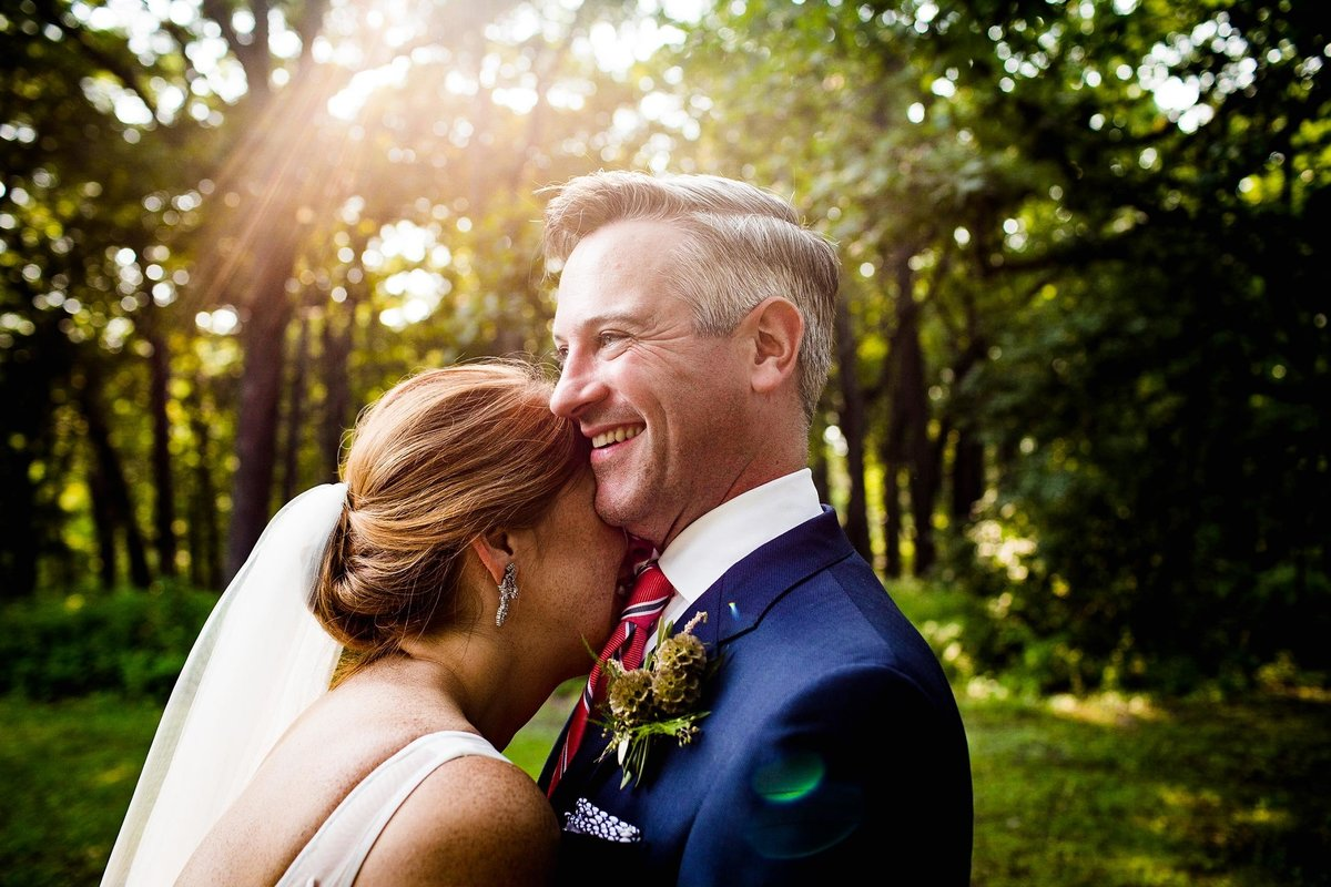 A couple laughs together during a forest preserve wedding.