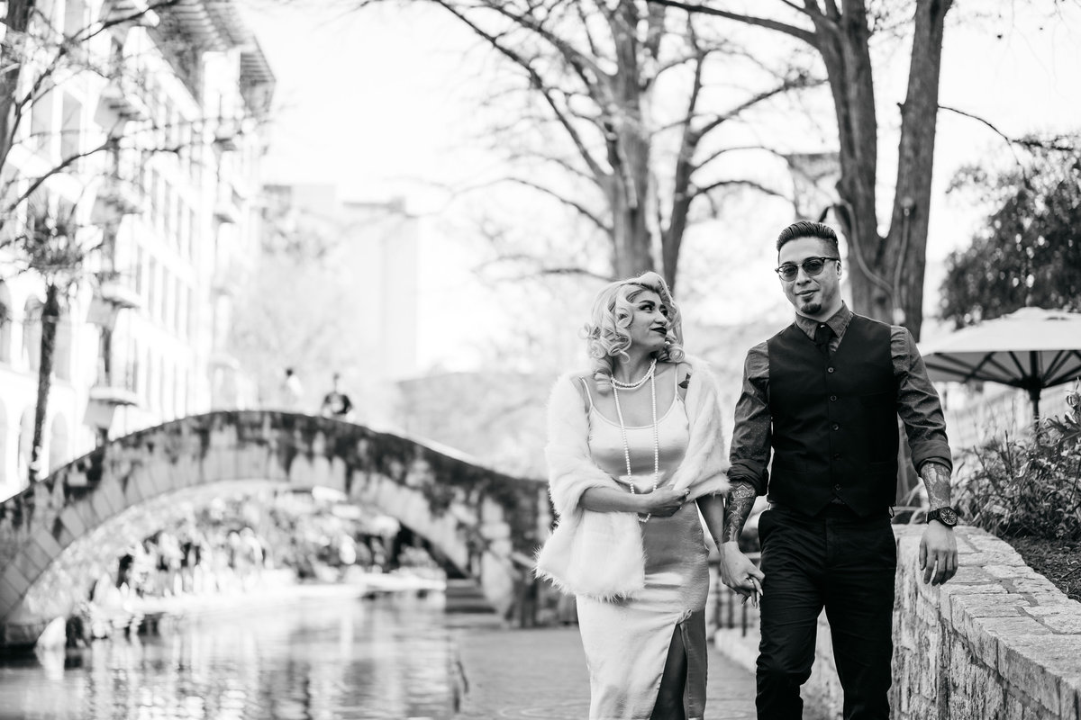 Black and white picture of engaged couple walking on the banks of the San Antonio River Walk downtown.