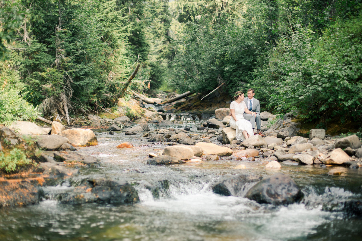 couple sits on rocks of river in mount rainier national forest