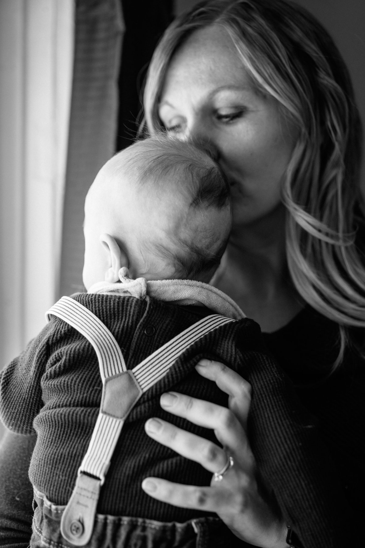 Mom kissing baby head by window during lifestyle newborn session in Hamilton.