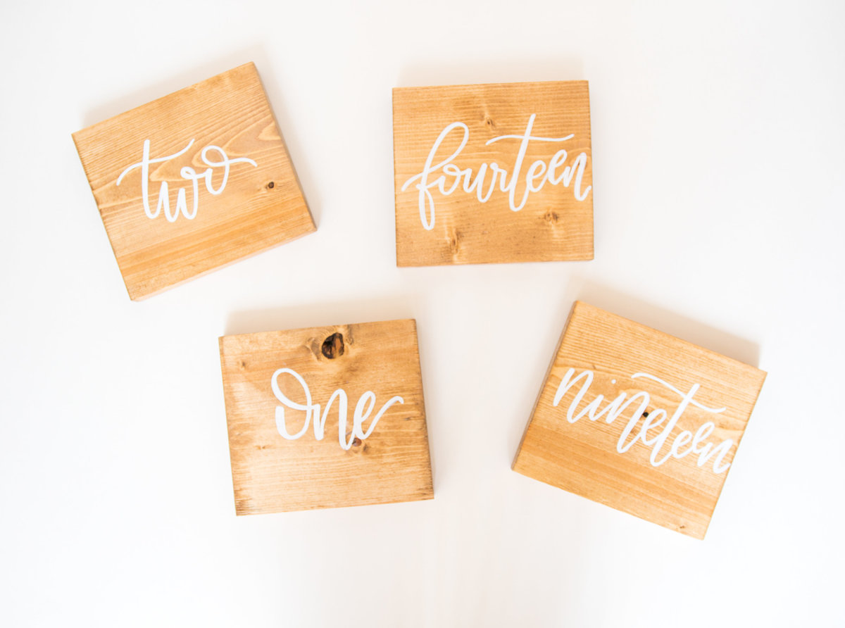 light wood table numbers with white calligraphy for weddings or events through Hue + FA Rentals