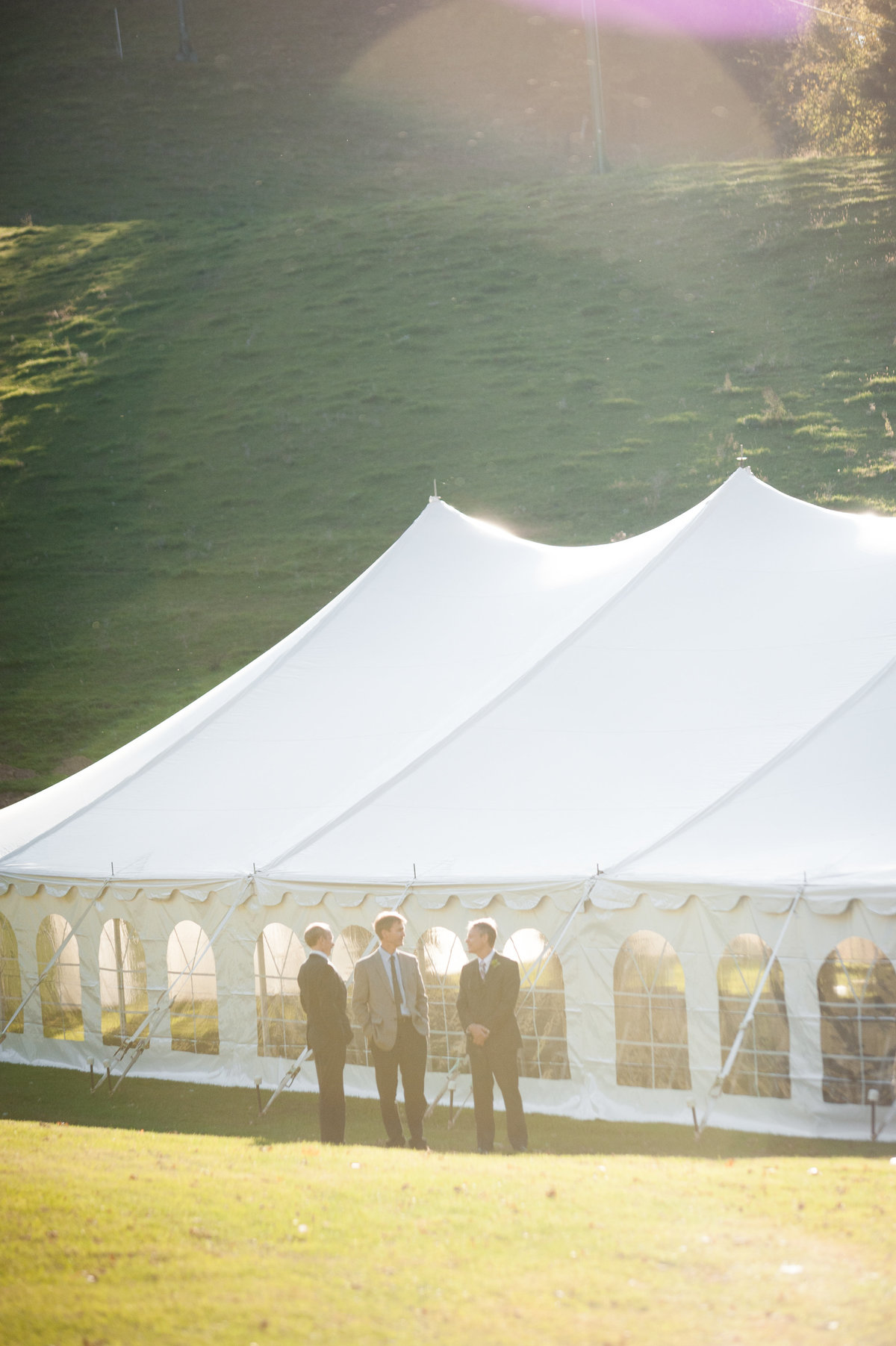 groomsmen standing outside white wedding tent