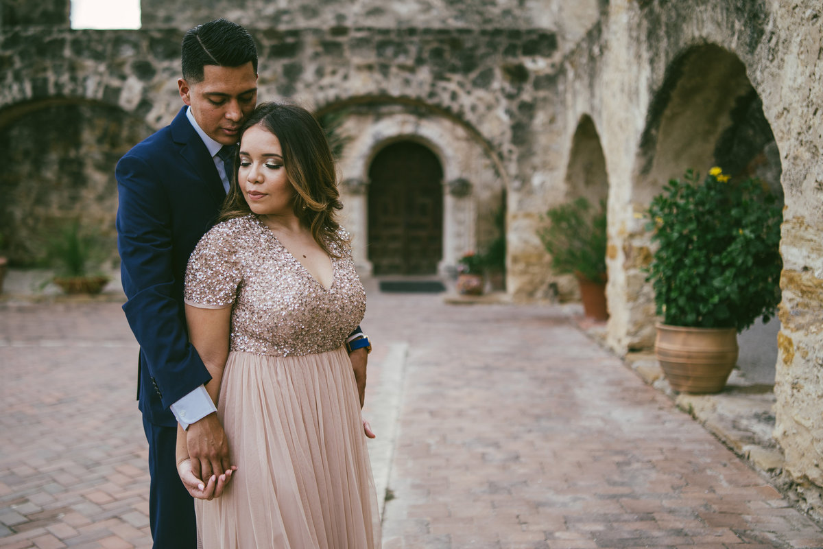 Gorgeous engaged hispanic couple standing by the arches at Mission San Jose in San Antonio.
