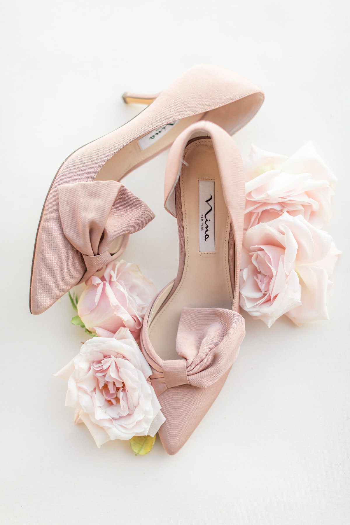Light pink wedding shoes with bows on the toes