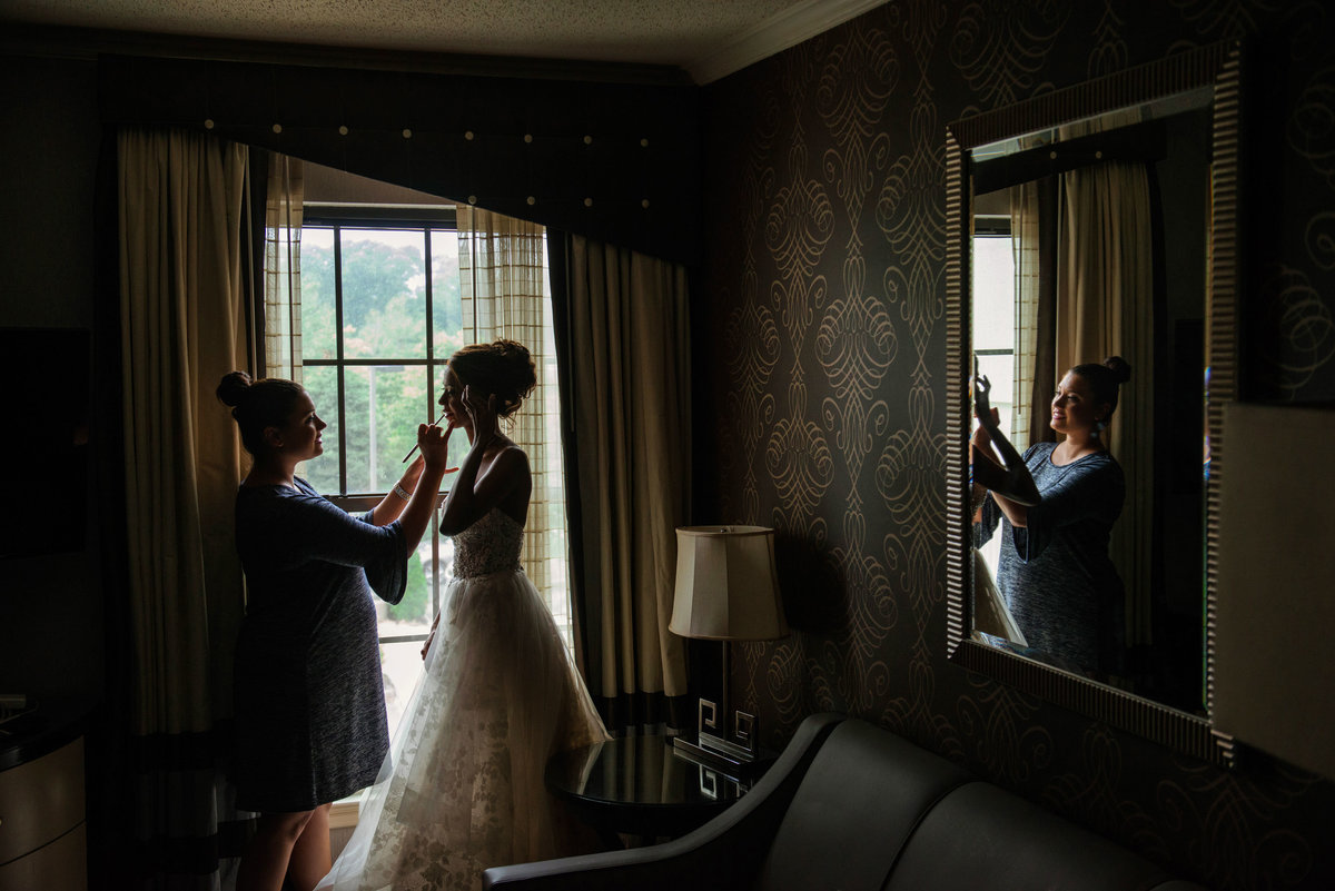 Bride getting ready in window at The Inn at Fox Hollow