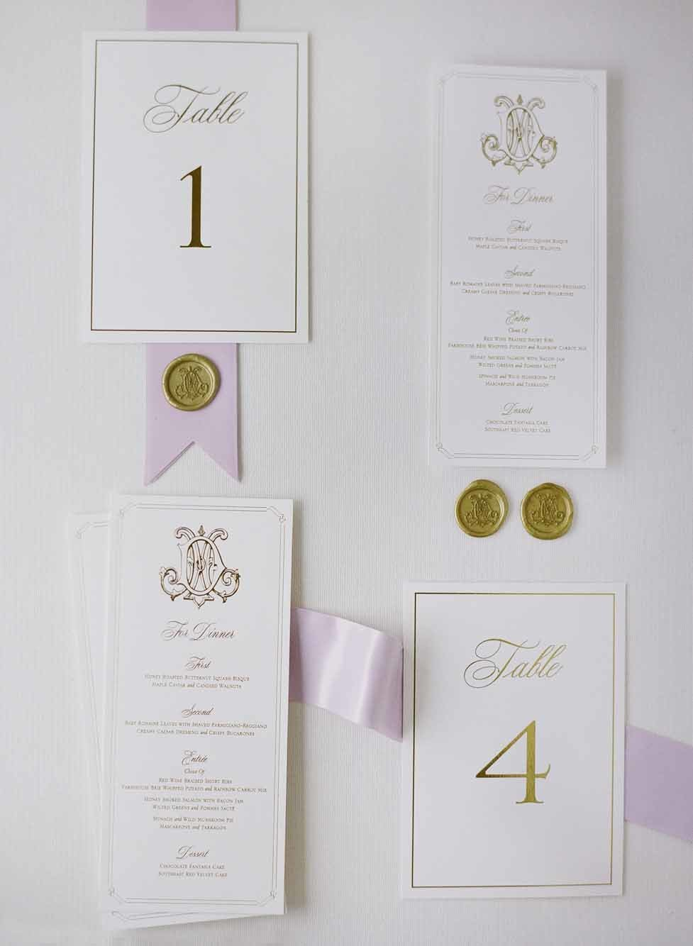 Beautiful wedding invitation suite flat-lay  with gold and purple accents.