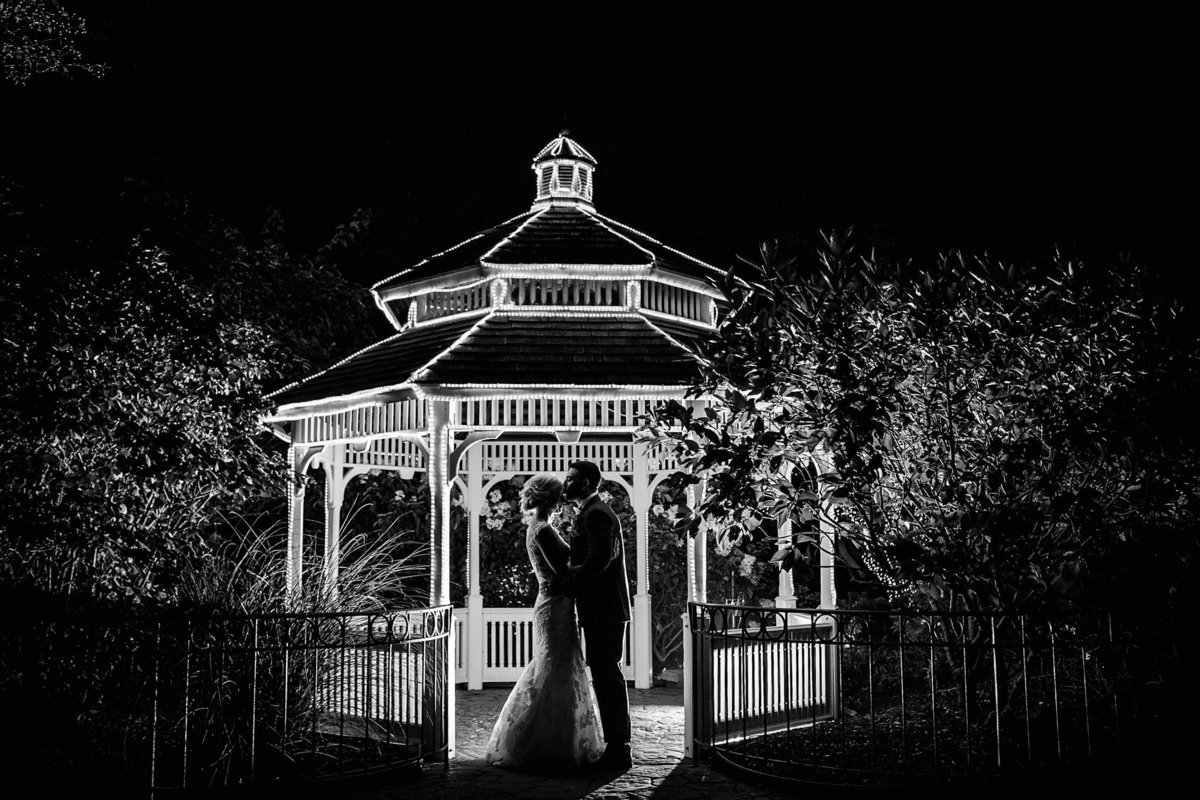 A couple kisses in silhouette during their Silver Lake Country Club wedding.