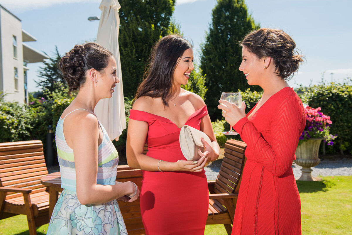 Female wedding guests wearing red dresses, standing in garden