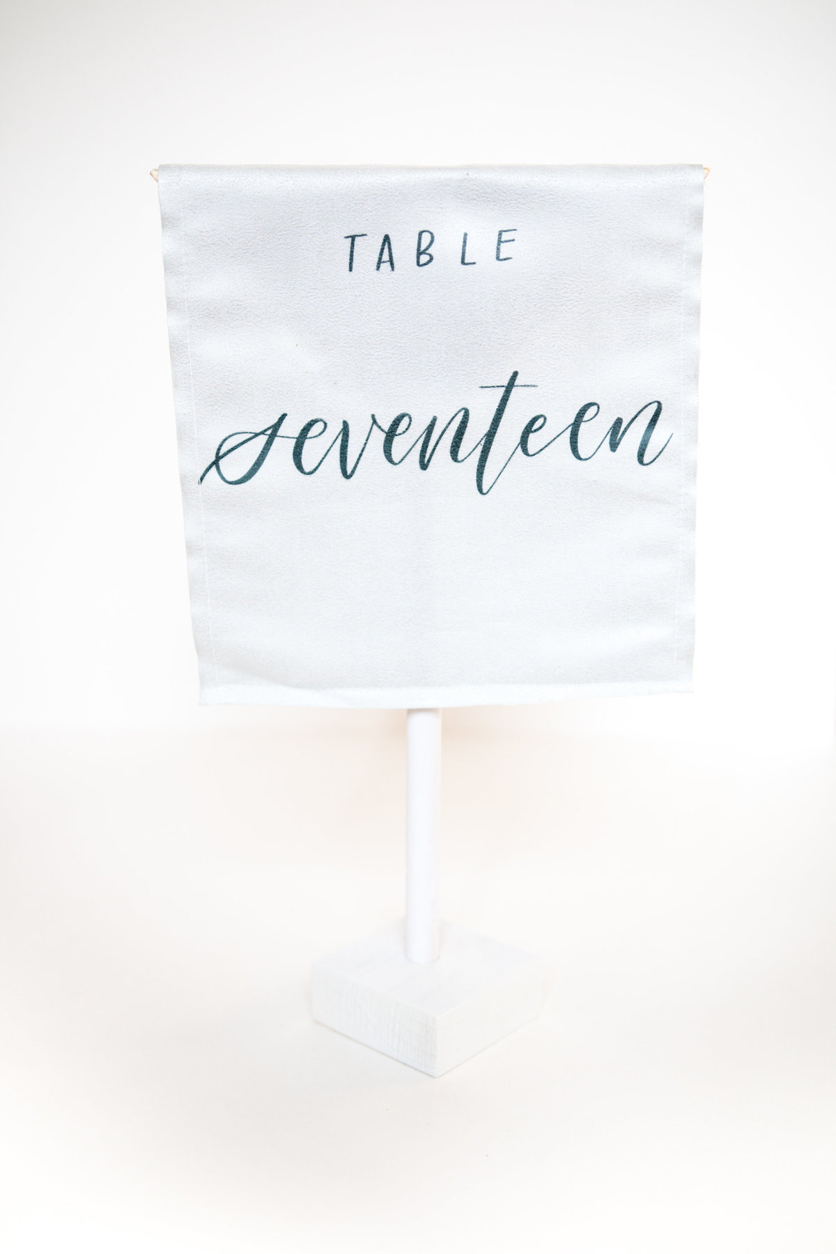 White velvet with calligraphy table numbers for weddings or events through Hue + FA Rentals