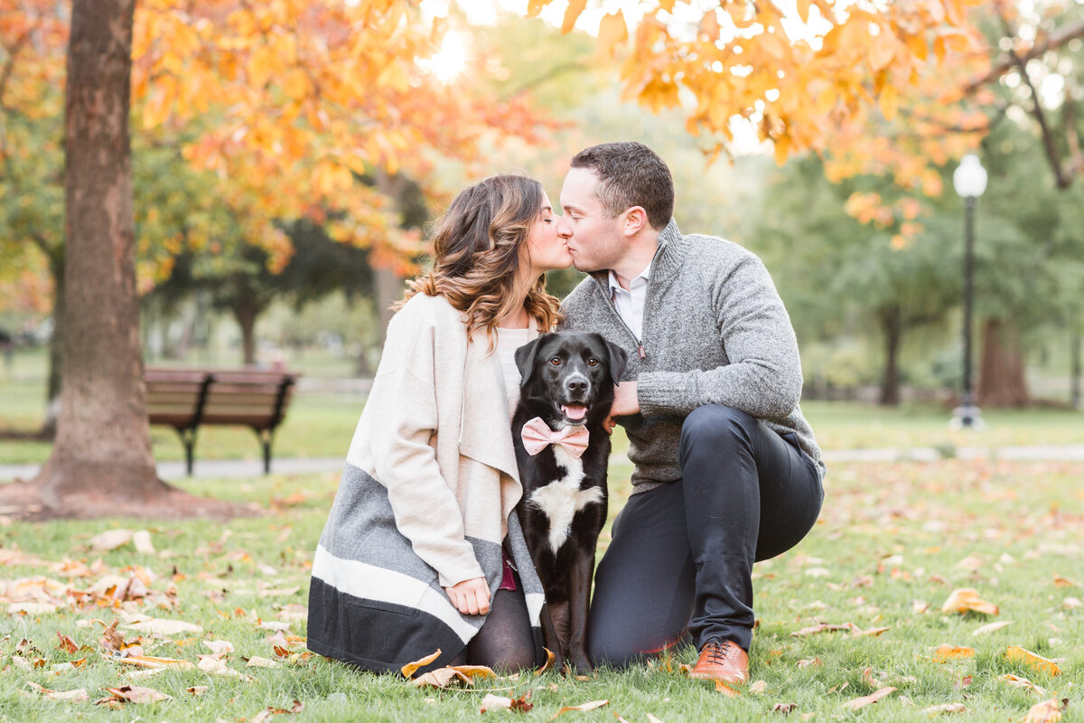 Couple kissing in the Boston Public Garden with their dog in the Fall